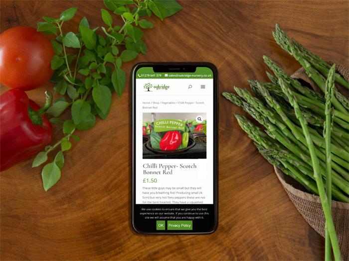 Oakridge Nursery website on a phone in a kitchen