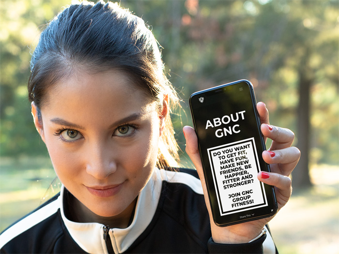 lady holding GNC Group Fitness website on a phone