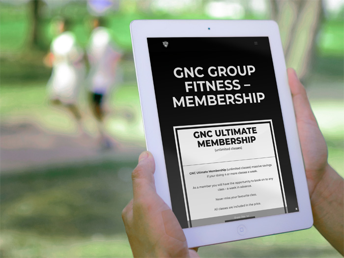 GNC Group Fitness website on a tablet in the park